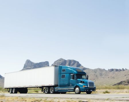 Large heavy goods freight truck speeding through Arizona desert