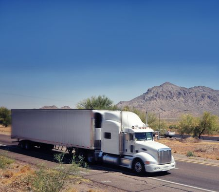 ciężarówka: Duże ciężarowe ładunków ciężarówek przyspieszenia poprzez Arizona pustyni Zdjęcie Seryjne
