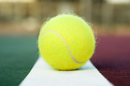 Tennis ball on clay court baseline photo