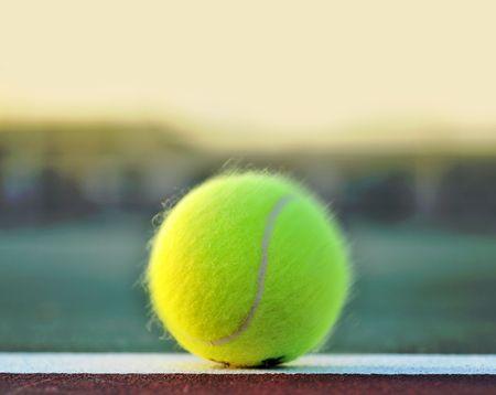 racquet: Tennis ball on clay court baseline