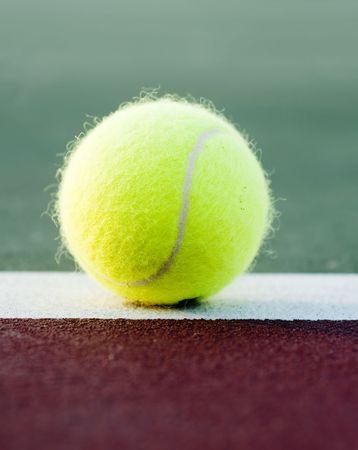 Tennis ball landing on clay court baseline photo