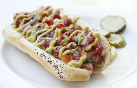 smothered: Fancy hot dog in bun smothered with mustard and ketchup
