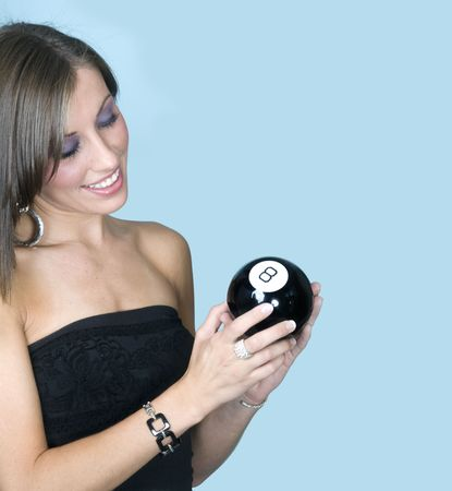 Attractive young woman looking at 8-ball for advice Stock Photo - 3533298
