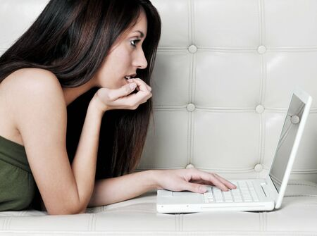 Attractive young woman using laptop at home   photo