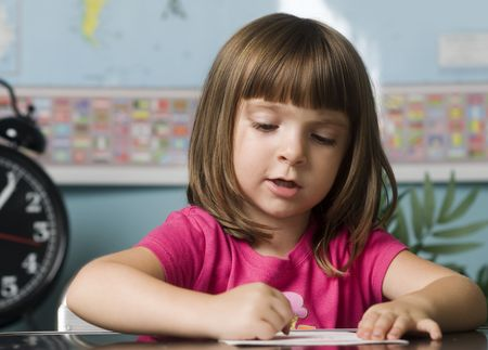 working hard: Young child working hard in class room Stock Photo