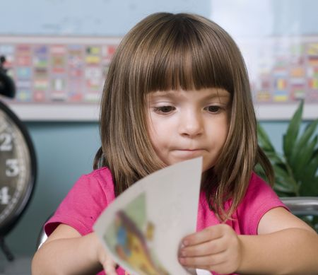 Young child turning the page of a book in a classroom Stock Photo - 3558794