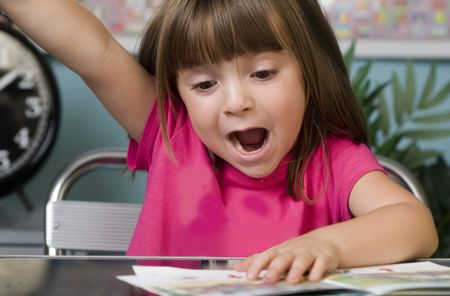 Young child raising her hand to answer a question Stock Photo - 3558830