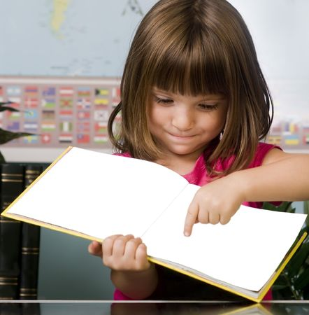 Young child pointing to a page in her reading book in class room photo