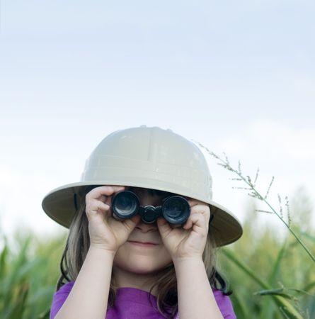Little girl looking through binoculars with safari hat