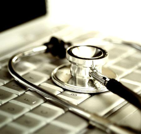 Plata estetoscopio sobre el teclado portátil Foto de archivo - 4758055