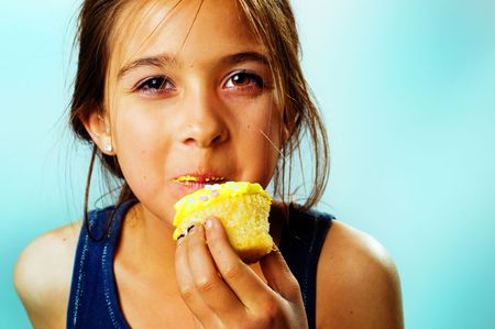 Pretty little girl having fun while eating a delicious birthday cupcake