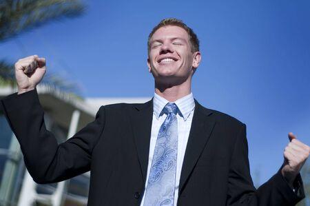 triumphant: Happy smiling triumphant business man