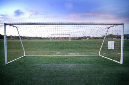 Soccer football field with focus on goal post and netting