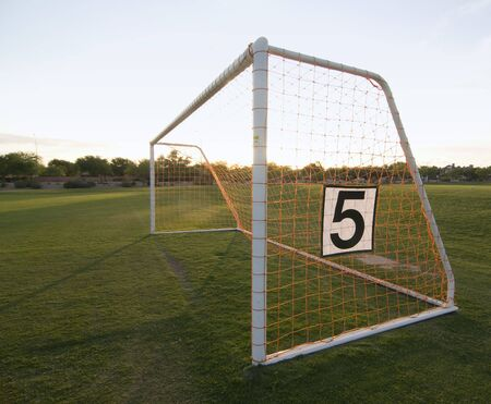 post: Soccer football field with focus on goal post and netting