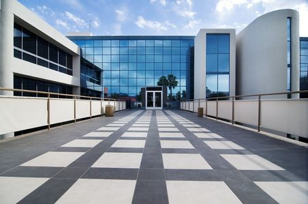 office building exterior: Modern commercial business exterior with glass reflection of clouds