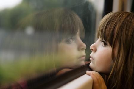 Little girl looking though window