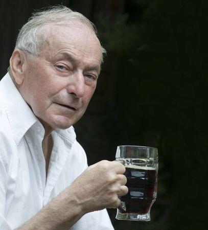 brew beer: Superior hombre bebiendo una cerveza fuera del pub.
