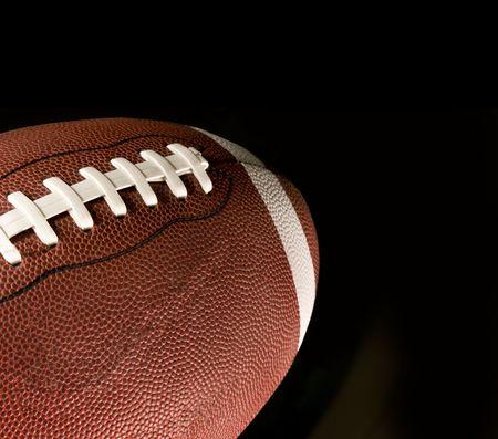 american football ball: American football against black background