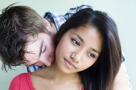 Young couple embrace and kiss in candid natural mome photo