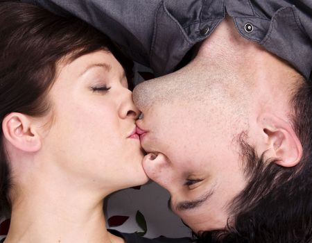Romantic loving kiss of couple laying down photo