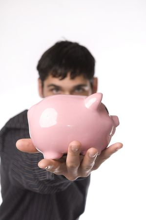Man holding a piggy bank with piggy bank in outstretched hand. photo
