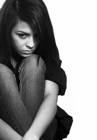 Sad young woman crouching on floor (acting) photo