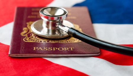 Stephoscope on passport. Health care in United Kingdom and EU.