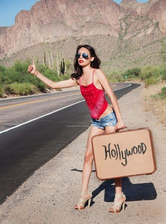 Beautiful young woman hitching a ride to Hollywood, USA photo