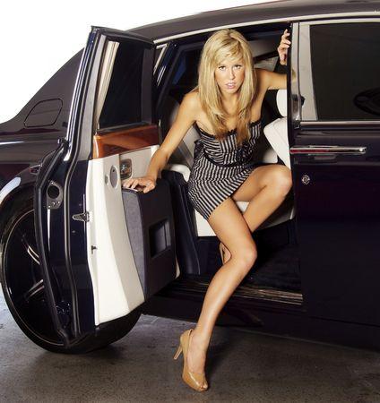atender: Hermosa mujer rubia saliendo de un coche de lujo para asistir a un evento de celebridad.