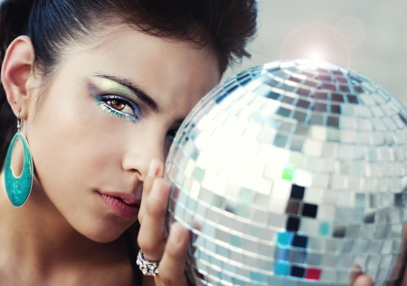 Beautiful young woman holding disco ball  Imagens