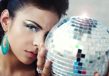 ディスコ ボールを保持している美しい若い女性