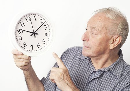 Mature older man looking and pointing at clock.  photo