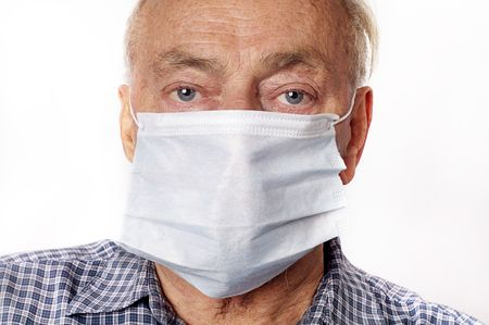 A mature man wearing a protective breath mask.  photo