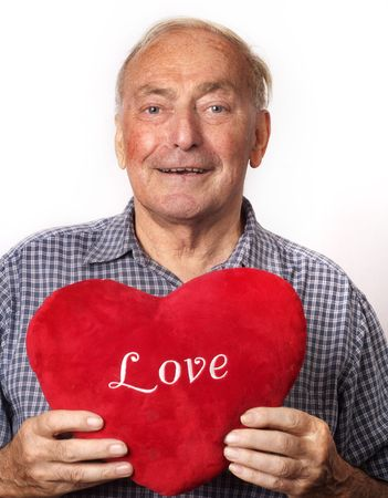 A mature man holding a red heart.  photo