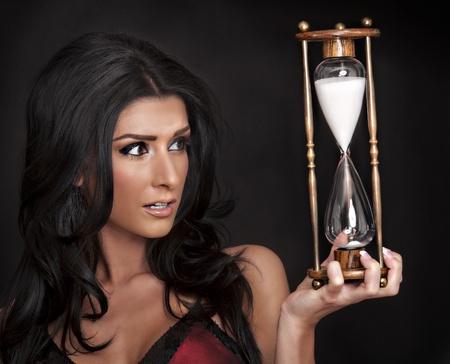woman clock: Hermosa mujer mirando el reloj de arena Foto de archivo