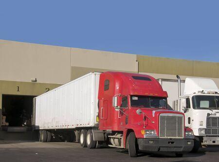Trucks loading and unloading at warehouse photo