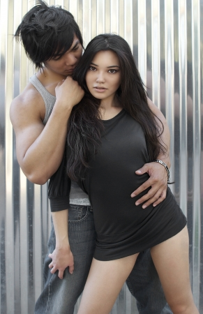 Attractive young Asian couple in embrace for fashion shoot