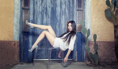 sexy asian woman:  Beautiful young Asian fashion model posing on chair Stock Photo