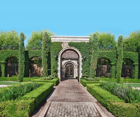 garden scenery: Brick stone garden path and Topiary leading to iron gate