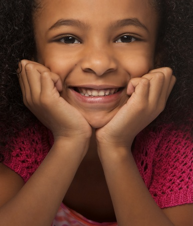 Close up photo of an adorable smiling little girl with curly hair