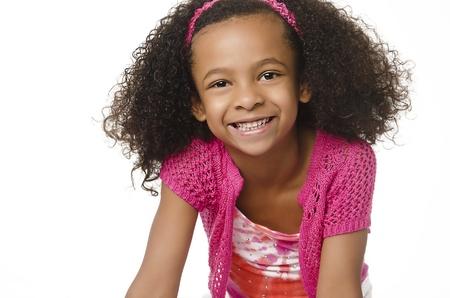 niños negros: Adorable niña sonriente con el pelo rizado