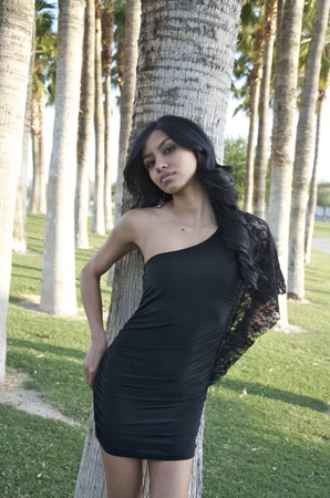 Pretty young woman wearing little black dress in park Stock Photo - 12952433