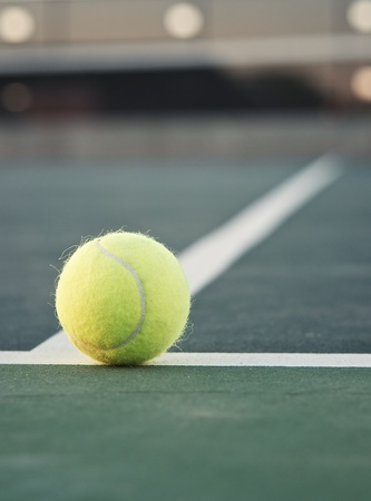 Tennis ball on baseline with net in background
