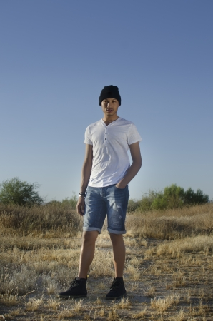 Young man wearing denim shorts, casual top and hat photo