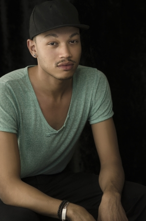 Low key portrait of young man wearing baseball cap
