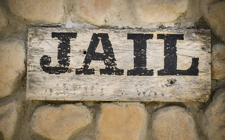 jail: Jail sign on wooden sign in cowboy town Stock Photo