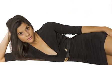 Beautiful young woman wearing black dress in fashion pose