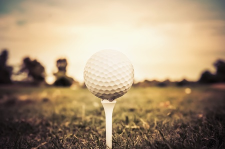 Retro aged nostalgia history golf ball on tee Stock Photo