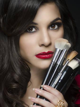 Beautiful woman holding makeup brushes