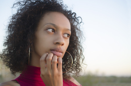 Young woman in thoughtful moment finger on mouth deciding  photo